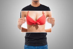 Male Holding Up Picture of Female Breasts