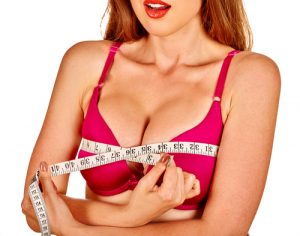Girl wearing in bra measures her breast measuring tape