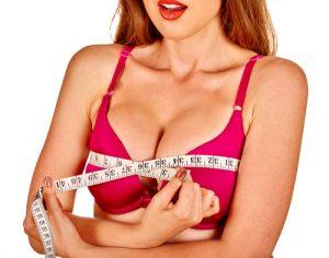 Girl wearing in bra measures her breast measuring tape
