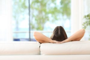 Rear view of a woman relaxing sitting on a couch with the hands on the head and looking outdoors