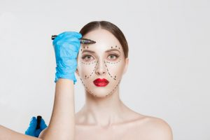 Doctor surgeon hand in glove draw wrinkle lines on Woman face