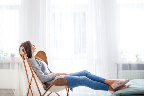Young woman at home sitting on modern chair near window relaxing in living room-img-blog