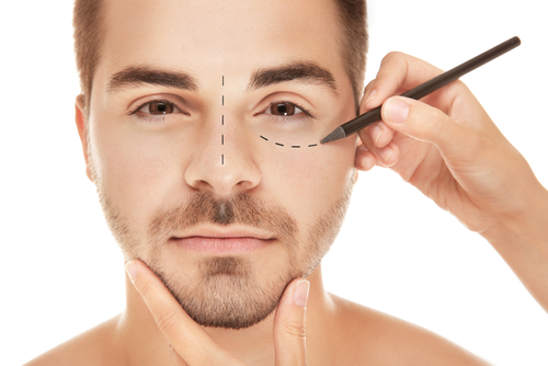 surgeon drawing marks on male face-img-blog